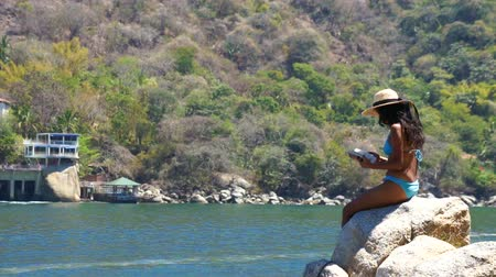 pozisyon : Young Woman sitting on a rock and reading a book Stok Video
