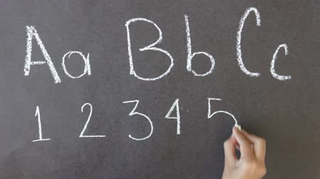 lousa : A person drawing a ABC and 123 illustration with chalk on a blackboard.