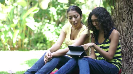 raiz : oung women looking at a tablet computer