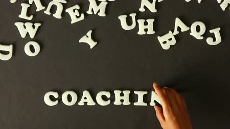 koç : A person spelling Coaching with plastic letters Stok Video