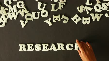 teoria : A person spelling Research with plastic letters
