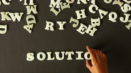 letras : A person spelling Solution with plastic letters