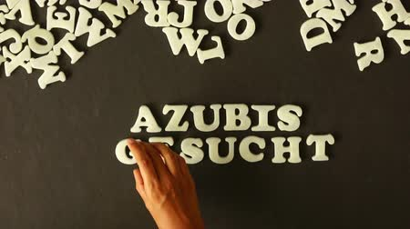 auxiliar : A person spelling Trainees Wanted spelling with plastic letters