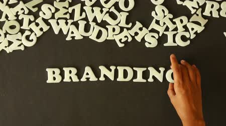 caracteres : A person spelling Branding with plastic letters Stock Footage