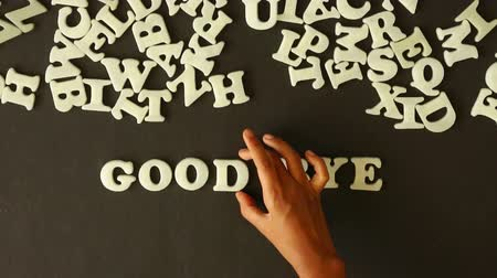 kapcsolatok : A person spelling goodbye with plastic letters