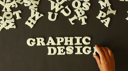 книгопечатание : A person spelling graphic design with plastic letters Стоковые видеозаписи