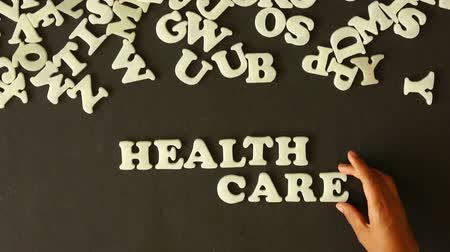 общественный : A person spelling health care with plastic letters Стоковые видеозаписи
