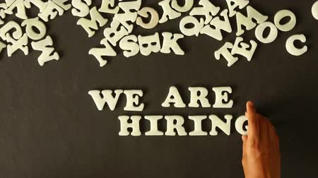 градация : A person spelling We are Hiring with plastic letters Стоковые видеозаписи