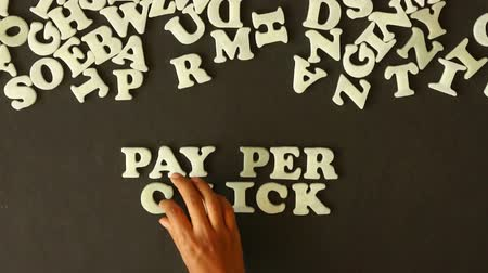bulmak : A person spelling Pay Per Click with plastic letters