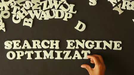 optimalizace : A Person spelling Search Engine Optimization with plastic letters