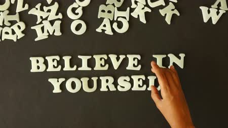 acreditar : A person spells Believe in yourself with plastic letters Vídeos