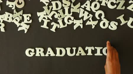 promoce : A person spelling Graduation with plastic letters