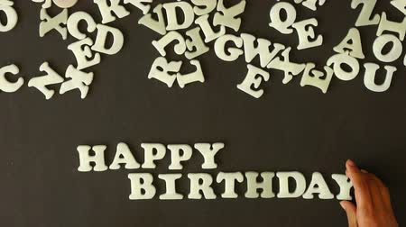 dilek : A person spelling Happy Birthday with plastic letters