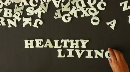 потеря : A person spelling Healthy Living with plastic letters