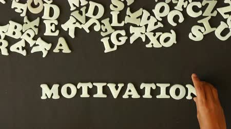 мотивация : A person spelling Motivation with plastic letters