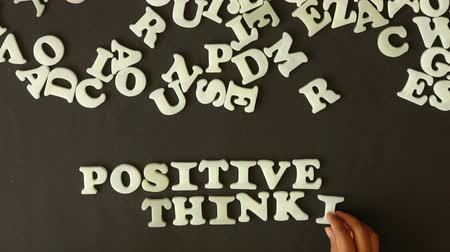 letras : A person spelling positive thinking with plastic letters