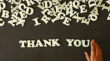 letras : A person spelling Thank you with plastic letters