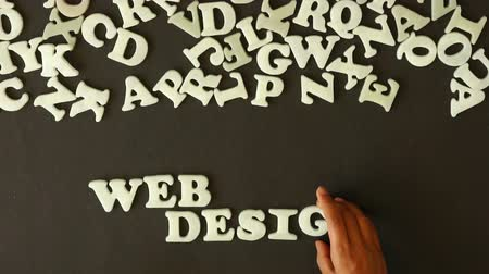 技术 : A person spelling web design with plastic letters