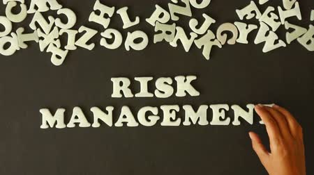 risco : A person spelling Risk Management with plastic letters Vídeos