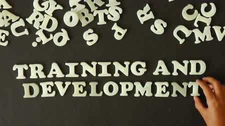 подготовке : A person spelling Training and Development with plastic letters