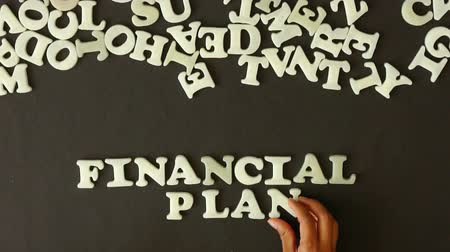 hesap : A person spelling Financial Plan with plastic letters