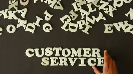 temsilci : A person spelling Customer Service with plastic letters