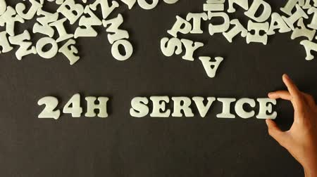 slib : A person spelling 24 Hour Service with plastic letters
