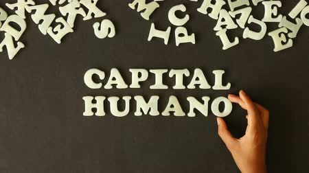 insan parmak : A person spelling Human capital (In Spanish)  with plastic letters