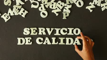 satysfakcja : A person spelling Quality Service with Plastic Letters (In Spanish)