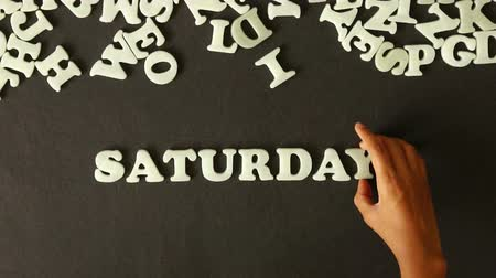 gün : A person spelling Saturday with Plastic letters Stok Video