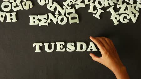 sobota : A person spelling Tuesday with Plastic letters