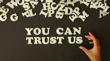 focalizada : A person spelling you can trust us with plastic letters
