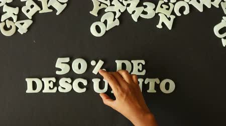barganha : A person spelling 50 percent Discount with Plastic letters (In Spanish)