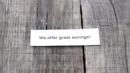 служба : A We offer Great Savings paper sign on wood background Стоковые видеозаписи