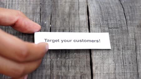 цель : A Target your Customers paper sign on wood background