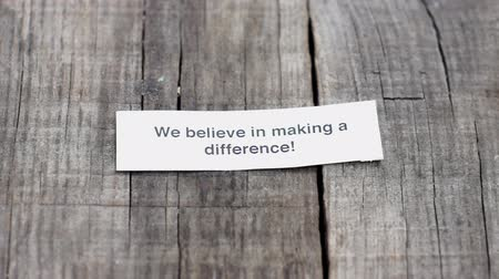 innováció : A We believe in Making a difference paper sign on wood background Stock mozgókép