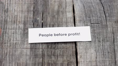 znalost : A People Before Profit paper sign on wood background Dostupné videozáznamy