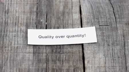 compromisso : A Quality over Quantity paper sign on wood background