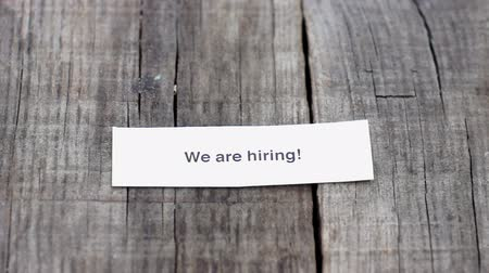 desemprego : A We are hiring paper sign on wood background