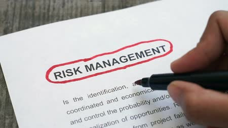 assess : Circling Risk Management with a red marker Stock Footage