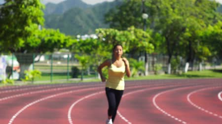 подготовке : A young woman running at a track in a stadium Стоковые видеозаписи