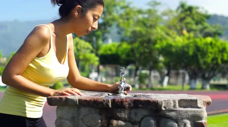 vodní sporty : A young woman running stopping at a water faucet to drink some water Dostupné videozáznamy