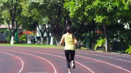 pista : A young woman running at a track in a stadium Vídeos