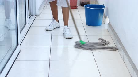 Пол : A young woman mopping the floor.