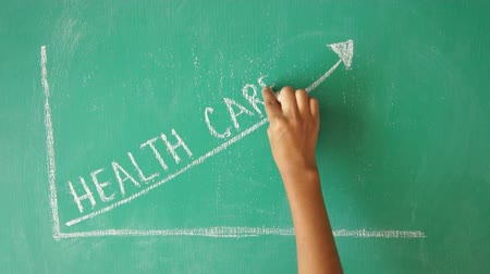 przychodnia : Person drawing a health care cost graph with chalk on a green board