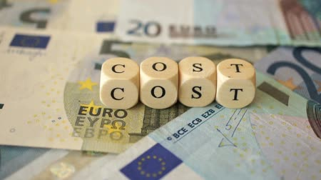 A dolly shot of several euro bills and the word Cost written with small wooden dices.