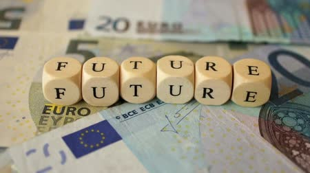 A dolly shot of several euro bills and the word Future written with small wooden dices.