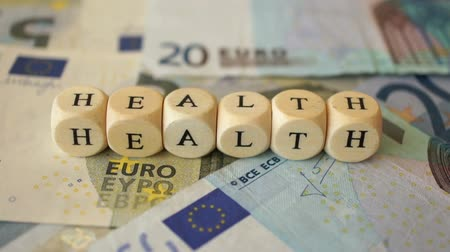 A dolly shot of several euro bills and the word Health written with small wooden dices.