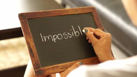 olasılık : A woman writing Impossible on a vintage chalk board Stok Video