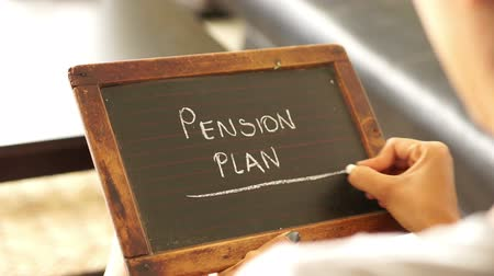 imposto : A woman writing Pension Plan on a vintage chalk board